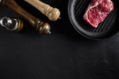 Fresh raw meat. Beef Tenderloin and marbled beef steaks on grill pan and frying board with seasoning, black background. Top view. Still life. Copy space. Flat Stock Image