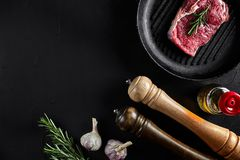 Fresh raw meat. Beef Tenderloin and marbled beef steaks on grill pan and frying board with seasoning, black background. Top view. Still life. Copy space. Flat Royalty Free Stock Photo