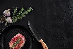 Fresh raw meat. Beef Tenderloin and marbled beef steaks on grill pan and frying board with seasoning, black background. Top view. Still life. Copy space. Flat Stock Photos