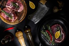 Fresh raw meat. Beef Tenderloin and marbled beef steaks on grill pan and frying board with seasoning, black background. Top view. Still Stock Photo