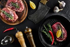 Fresh raw meat. Beef Tenderloin and marbled beef steaks on grill pan and frying board with seasoning, black background. Fresh raw meat. Beef Tenderloin steak and Royalty Free Stock Photos