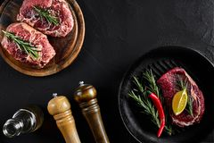 Fresh raw meat. Beef Tenderloin and marbled beef steaks on grill pan and frying board with seasoning, black background. Fresh raw meat. Beef Tenderloin steak and Royalty Free Stock Photo