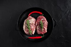 Fresh raw meat. Beef Tenderloin and two marbled beef steaks on grill pan and frying board with seasoning, black. Fresh raw meat. Beef Tenderloin steak and two Royalty Free Stock Images