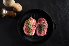 Fresh raw meat. Beef Tenderloin and two marbled beef steaks on grill pan and frying board with seasoning, black. Fresh raw meat. Beef Tenderloin steak and two Stock Photography