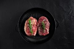 Fresh raw meat. Beef Tenderloin and two marbled beef steaks on grill pan and frying board with seasoning, black. Fresh raw meat. Beef Tenderloin steak and two Royalty Free Stock Photos