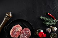 Fresh raw meat. Beef Tenderloin and two marbled beef steaks on grill pan and frying board with seasoning, black. Background top view. Still life. Copy space Royalty Free Stock Image