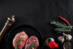 Fresh raw meat. Beef Tenderloin and two marbled beef steaks on grill pan and frying board with seasoning, black. Background top view. Still life. Copy space Royalty Free Stock Photography