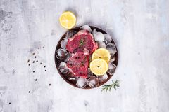Fresh raw meat beef on a wooden plate with lemon slice and ice. Lean proteins. Fresh raw meat beef on a wooden plate with lemon slice and ice on a concrete Stock Photos