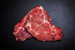 Fresh raw meat on black board. With spices and herbs Stock Photos