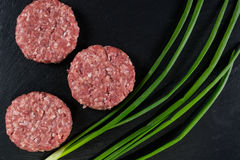 Fresh raw meat burger  cutlet on the black slate board with green onion. Top view Royalty Free Stock Photos