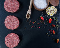 Fresh raw meat burger cutlet on the black slate board with herbs and spices for background. Stock Image