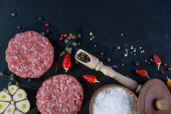 Fresh raw meat burger cutlet on the black slate board with herbs and spices for background. Copy space, top view Stock Photography