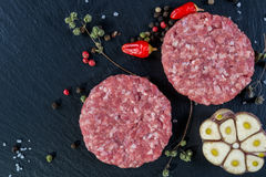 Fresh raw meat burger cutlet on the black slate board with herbs and spices for background. Copy space, top view Royalty Free Stock Photos