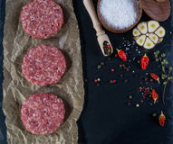 Fresh raw meat burger cutlet on the black slate board with herbs and spices for background. Royalty Free Stock Photo