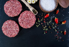Fresh raw meat burger cutlet on the black slate board with herbs and spices for background. Stock Photos