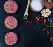 Fresh raw meat burger cutlet on the black slate board with herbs and spices for background. Royalty Free Stock Photography