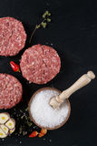 Fresh raw meat burger cutlet on the black slate board with herbs and spices for background. Royalty Free Stock Images