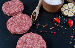 Fresh raw meat burger cutlet on the black slate board with herbs and spices for background. Stock Images