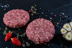 Fresh raw meat burger cutlet on the black slate board with herbs and spices for background. Copy space, top view .Selective focus Stock Photography