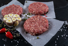 Fresh raw meat burger cutlet on the black slate board with herbs and spices for background. Stock Photography