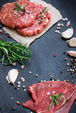 Fresh raw meat and burger cutlets. From the farmers market on a black grunge table. Selective focus Stock Image
