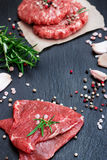 Fresh raw meat and burger cutlets. From the farmers market on a black grunge table. Selective focus Royalty Free Stock Image