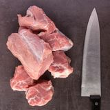 Fresh raw meat and a butcher knife lies on the surface of a dark. Stone. Cooking concept Stock Image