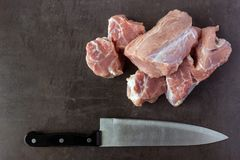Fresh raw meat and a butcher knife lies on the surface of a dark. Stone. Cooking concept Royalty Free Stock Photo