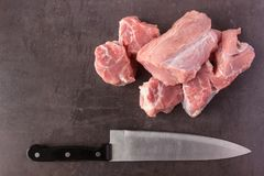 Fresh raw meat and a butcher knife lies on the surface of a dark. Stone. Cooking concept Stock Photos