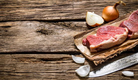 Fresh raw meat with a butcher knife and a onion. Stock Photography