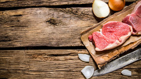 Fresh raw meat with a butcher knife and a onion. Royalty Free Stock Photo