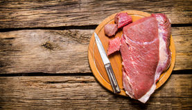 Fresh raw meat with a butcher knife. Stock Photo