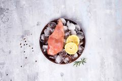 Fresh raw meat chicken breast on a wooden plate with lemon slice and ice. Lean proteins. Fresh raw meat chicken breast on a wooden plate with lemon slice and Royalty Free Stock Photography