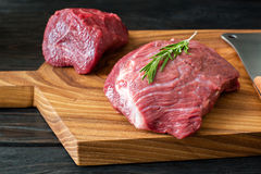 Fresh raw meat on chopping board with rosemary Royalty Free Stock Photo