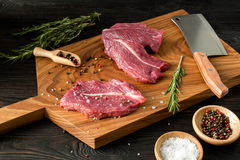Fresh raw meat on chopping board with rosemary, salt, pepper. Fresh meat on chopping board with knife and rosemary. Raw meat. three peece of beef ready for Royalty Free Stock Photography