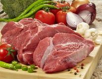 Fresh raw meat on cutting board. Raw beef meat on cutting board and fresh vegetables on wooden table Royalty Free Stock Photo