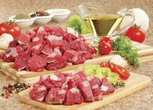 Fresh raw meat on cutting board. Raw beef meat on cutting board and fresh vegetables on wooden table Stock Photos
