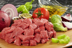 Fresh raw meat on cutting board. Raw beef meat on cutting board and fresh vegetables on wooden table Royalty Free Stock Photos