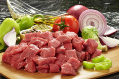 Fresh raw meat on cutting board. Raw beef meat on cutting board and fresh vegetables on wooden table Royalty Free Stock Image