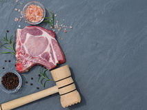 Fresh raw meat and hammer on the table. Top in natural stone Royalty Free Stock Photography