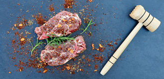 Fresh raw meat and hammer on the table top. In natural stone Royalty Free Stock Photo
