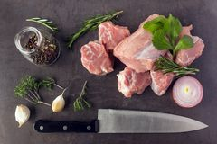 Fresh raw meat with herbs, spices and a butcher knife lies on th. E surface of a dark stone. Cooking concept Royalty Free Stock Image