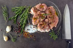 Fresh raw meat with herbs, spices and a butcher knife lies on th. E surface of a dark stone. Cooking concept Stock Photo