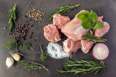 Fresh raw meat with herbs and spices  lies on the surface of a d. Ark stone. Cooking concept Stock Image
