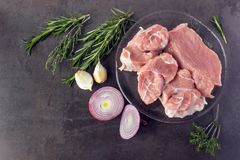 Fresh raw meat with herbs and spices  lies on the surface of a d. Ark stone. Cooking concept Royalty Free Stock Photography