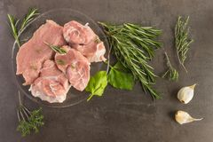 Fresh raw meat with herbs and spices  lies on the surface of a d. Ark stone. Cooking concept Stock Photos