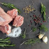 Fresh raw meat with herbs and spices  lies on the surface of a d. Ark stone. Cooking concept Stock Photography