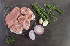 Fresh raw meat with herbs and spices  lies on the surface of a d. Ark stone. Cooking concept Stock Images