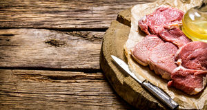 Fresh raw meat with knife and oil on a wooden stand. Royalty Free Stock Photo