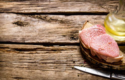 Fresh raw meat with knife and oil on a wooden stand. Stock Photos